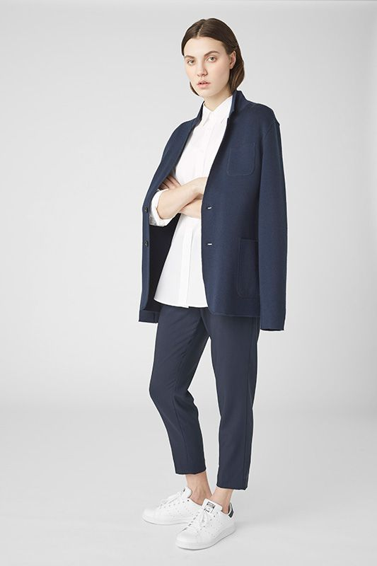 A woman in a simple navy blazer over a white shirt with navy pants, all made by Everlane. She also wears white sneakers.