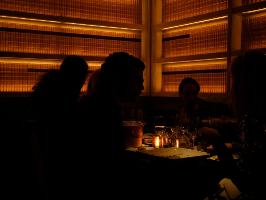 Silhouettes of diners are illuminated by candlelight in a dimly lit restaurant, against a backdrop of yellow-orange books