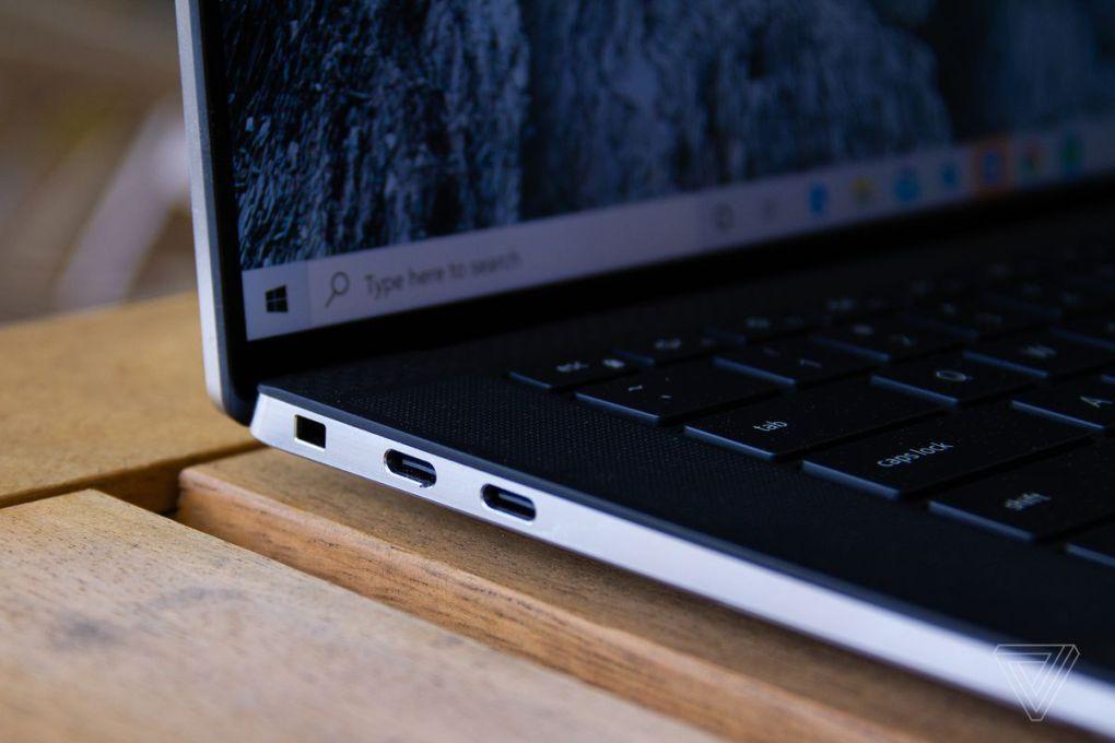 Chi tiết các cổng kết nối của laptop Dell XPS 15 ngồi bàn gỗ.