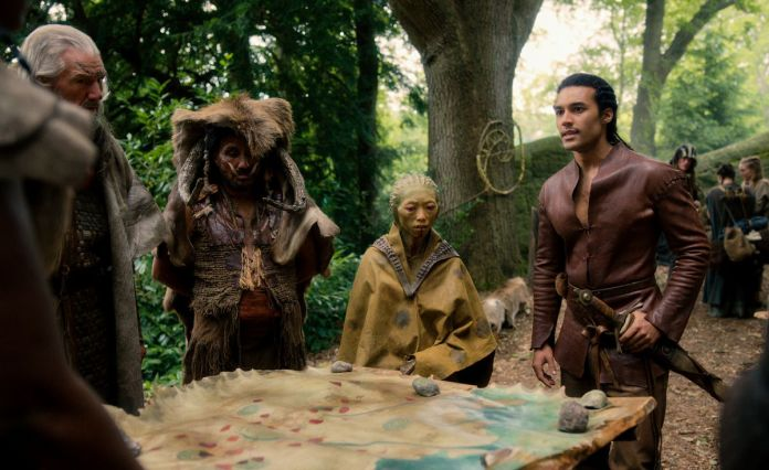 DEVON TERRELL as ARTHUR stands around a war map planning with his fellow kingdom dwellers
