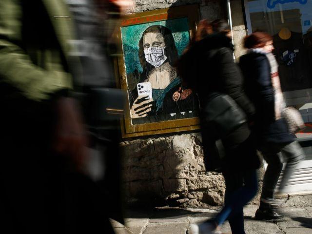 People walk by a poster depicting Leonardo da Vinci's Mona Lisa wearing a protective facemask in a street of Barcelona on February 18, 2020,