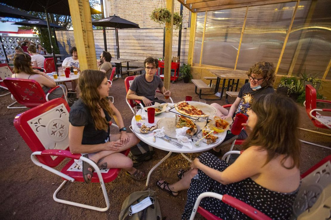 People eating sitting on a patio table.