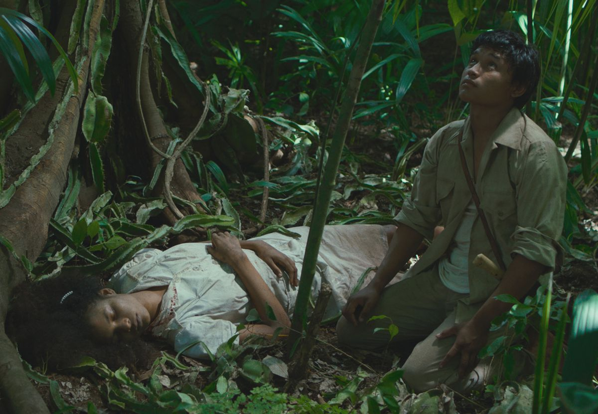 A woman in white lies in the jungle as a young man kneels next to her, looking up