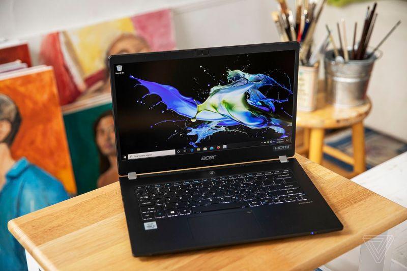 L'Acer Travelmate P6 su un tavolino aperto, leggermente inclinato a destra, visto dall'alto.  Lo schermo visualizza un motivo verde e giallo su sfondo nero.