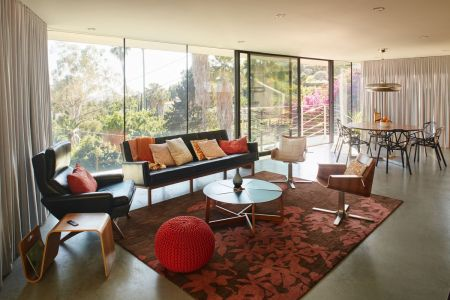 Living room rug ideas and tips  How to choose the right one   Curbed At a concrete ciffside home in LA  an area rug plays up the space s accent  colors while adhering to the trick of putting the front legs and side  chairs on