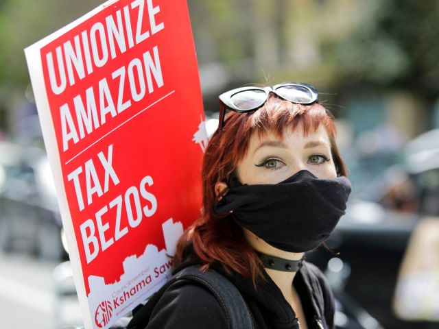 "A protester in a breathing mask carries a sign reading ""Unionize Amazon, tax Bezos."""