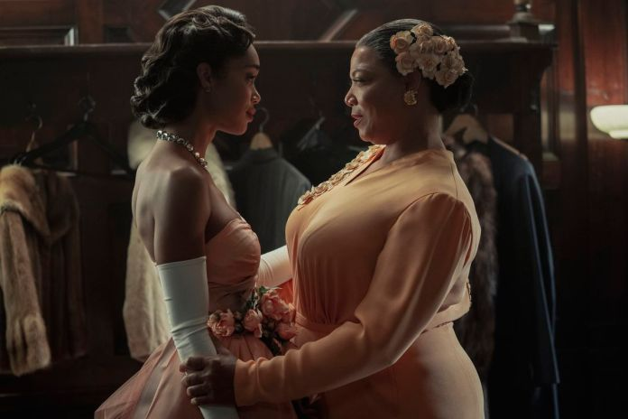 An older black woman in a conservative peach dress speaks to a younger black woman in a bridesmaid's-style peach dress in front of a group of hanging coats.
