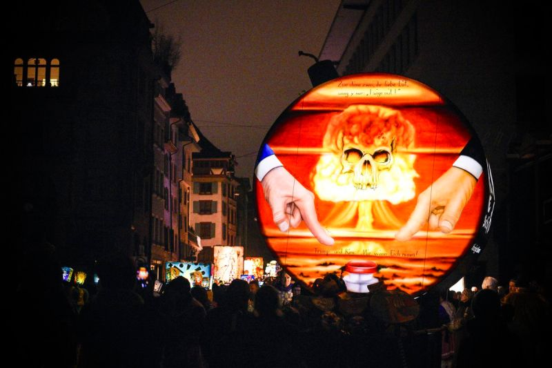 A painting on a float representing President Trump and Kim Jong-Un pushing the nuclear red button at the Basel Carnival in Switzerland, on July 25, 2018.