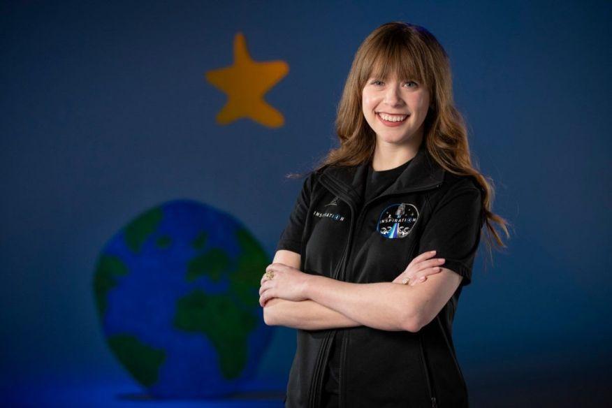 Белая женщина с длинными светло-каштановыми волосами улыбается и стоит, скрестив руки, перед стеной, нарисованной планетой Земля и звездой.
