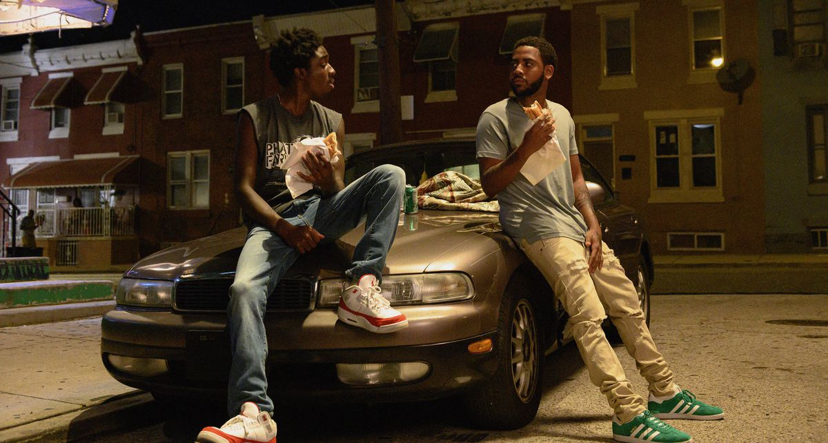 Caleb McLaughlin as Cole and Jharrel Jerome as Smush sit on a car's hood at night, eating paper-wrapped sandwiches