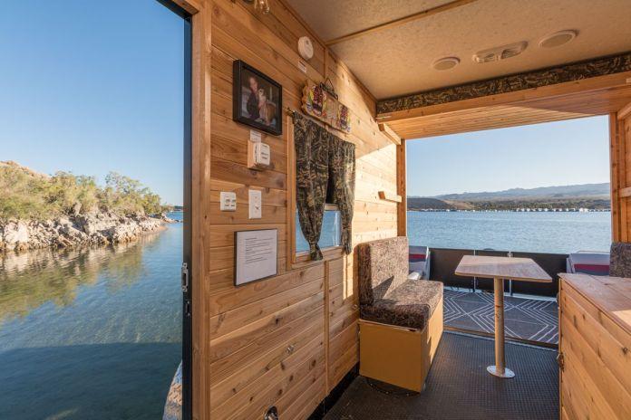 Внутри лодки есть обшитые деревянными панелями стены, столовая, стол и двери, выходящие на воду снаружи.