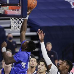 BYU forward Gideon George, left, shoots past guard Gonzaga Joel Ayayi, right, during the first half of an NCAA college basketball game in Spokane, Wash. On Thursday, Jan. 7, 2021.
