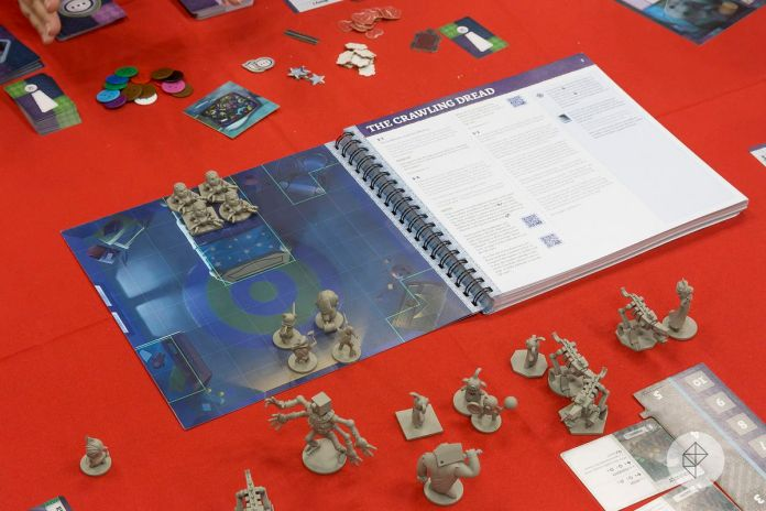 A ring-bound book spread on a table with miniatures of spiders and animated teddy bears placed directly on it. The facing page contains all the rules pertinent to that adventure, as well as flavor text.