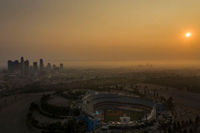 An aerial view of Dodger Stadium and the downtown Los Angeles skyline obscured by smoke, ash, and smog