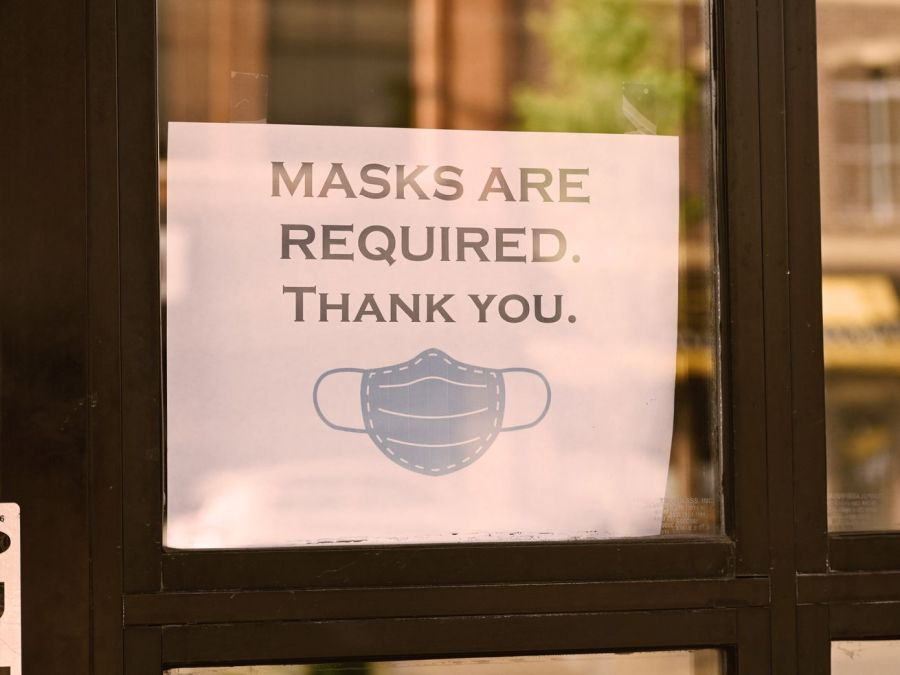 "Paper sign in a window reading ""Masks are required. Thank you."" with an image of a disposable paper mask."