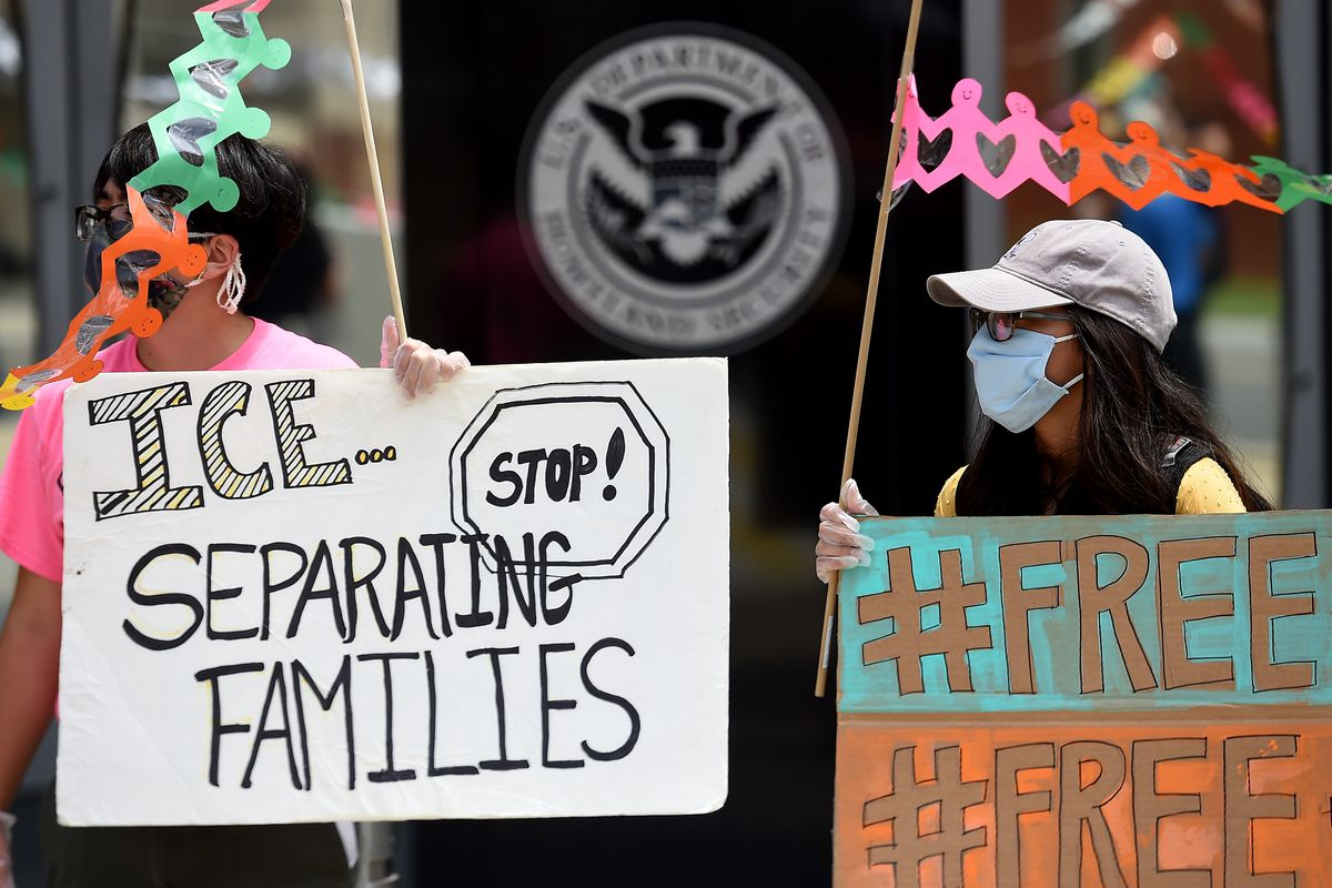 "Protesters carry signs that read, ""#Free"" and ""ICE - Stop separating families!"""