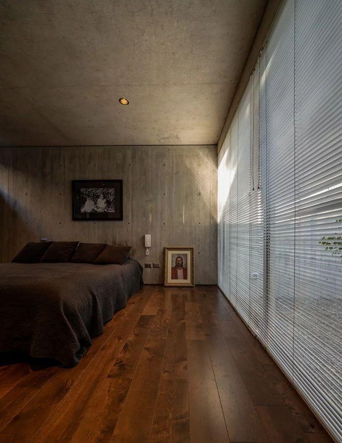 Спальня в подвале с деревянными полами, бетонным потолком и стеной, а также фасадом из стеклянных стен, покрытых жалюзи. Кровать с серым постельным бельем сидит я в центре.