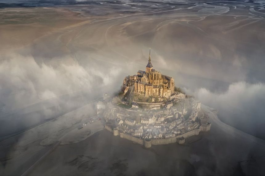 "<em>""The famous monastery of Mont Saint Michel during a foggy morning.""</em>"
