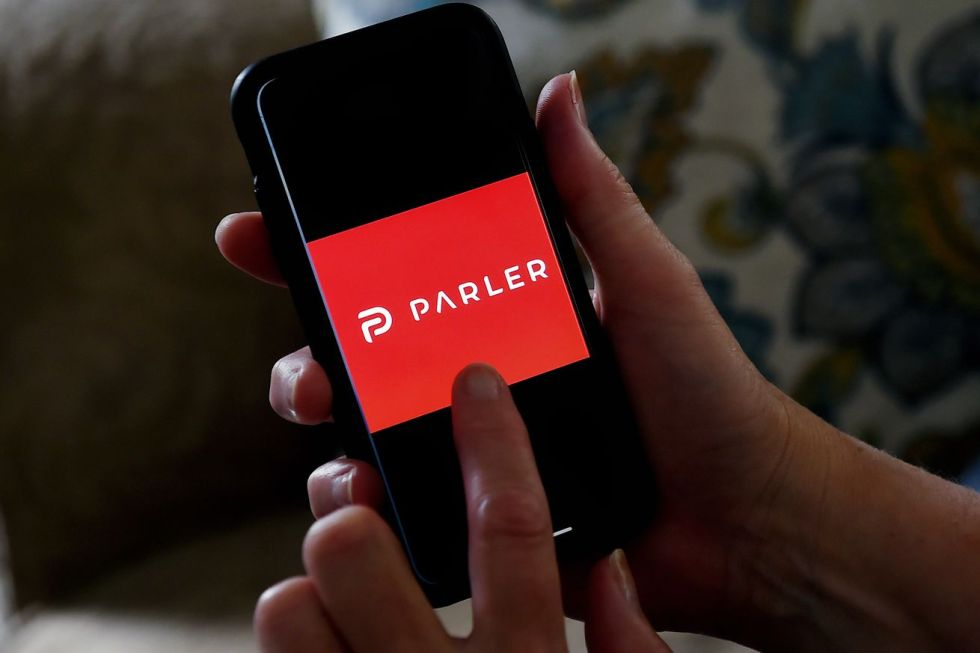 This illustration picture shows social media application logo from Parler displayed on a smartphone in Arlington, Virginia on July 2, 2020. - Amid rising turmoil in social media, recently formed social network Parler is gaining with prominent political conservatives who claim their voices are being silenced by Silicon Valley giants.