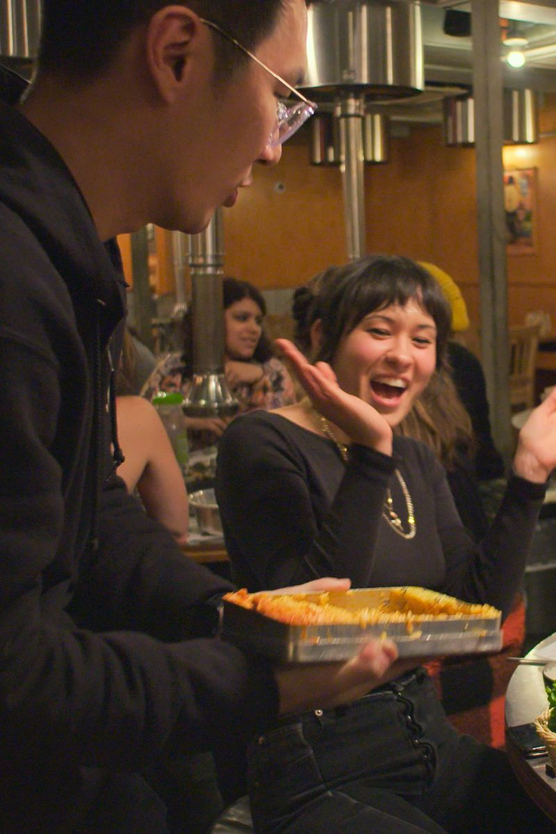 A woman claps in excitement as a dish is presented to her by a server.