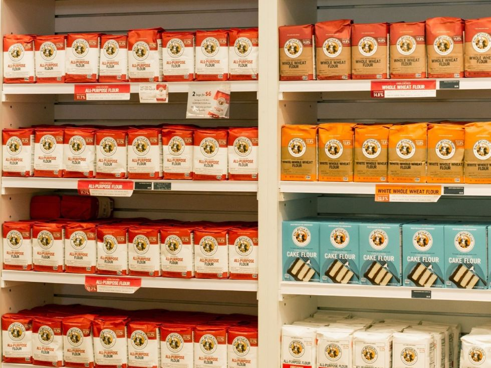 Bags of King Arthur-branded products on store shelves.