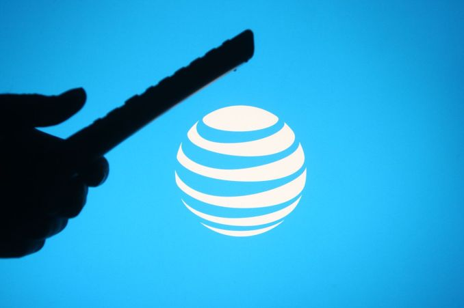 In this photo illustration the AT&T logo is seen behind a...
