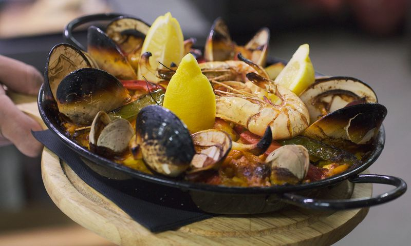 A black dish of shellfish presented on a tray.