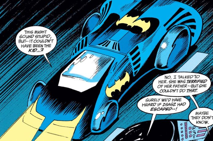 The Batmobile drives through city streets. It's a wide vehicle with two huge upswept rear spoilers, its hood shaped like the Batman cowl with headlights for the eyes, and THREE yellow batsymbols both doors and its rear hood. As seen in Batman: Shadow of the Bat #1, DC Comics (1992).