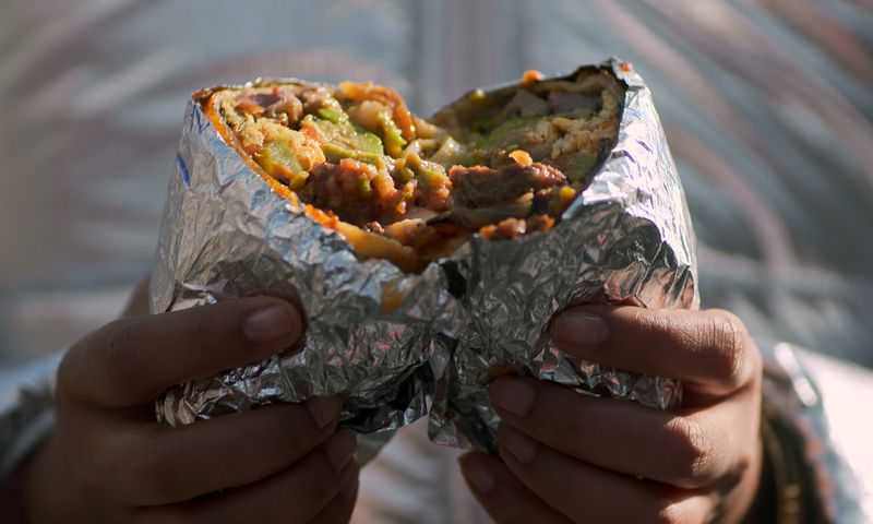 Two hands hold a foil wrapped burrito being torn in half.