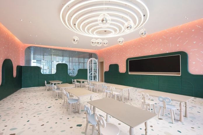 Классная комната с зелеными, розовыми стенами, серыми столами и стульями и терраццо-полами.