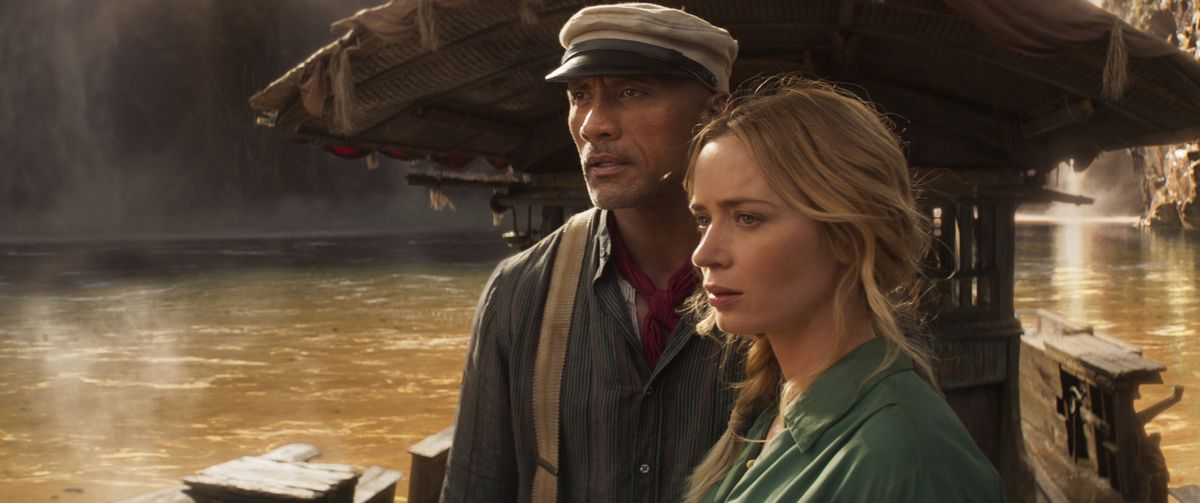 Dwayne Johnson in a hat and Emily Blunt look off their ship in Jungle Cruise