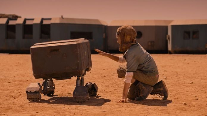 Brooklynn Prince as Remmy kneels to touch a boxy four-legged robot in Settlers