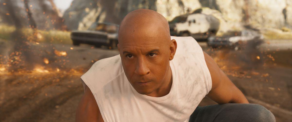Dom (Vin Diesel) crouches on one knee as car debris blows up around him in F9