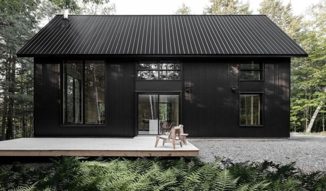 Black chalet with wooden deck