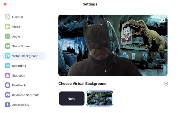 image showing a zoom user wearing a batman mask in front of a batcave virtual background