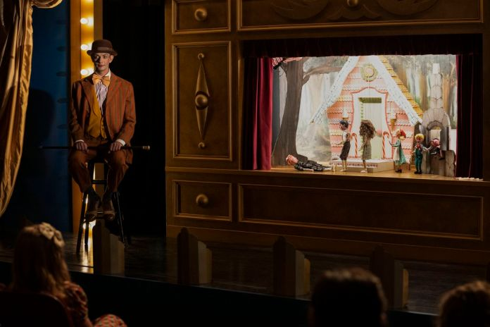 A man in vaudeville makeup sits on a stage with a well-lit puppet show in Ratched