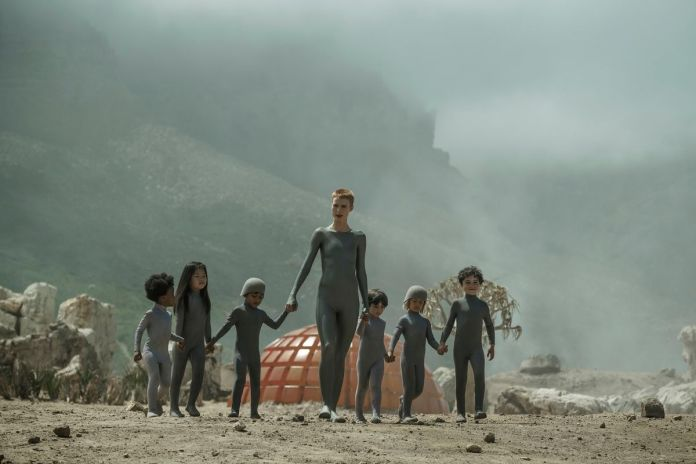 Amanda Collin leads a series of children in grey jumpsuits in Raised By Wolves