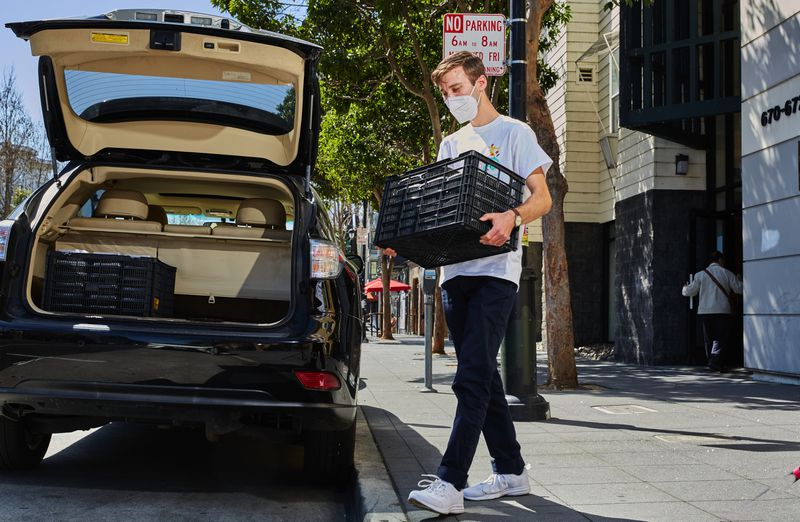 A man loads a crate into the trunk of a car