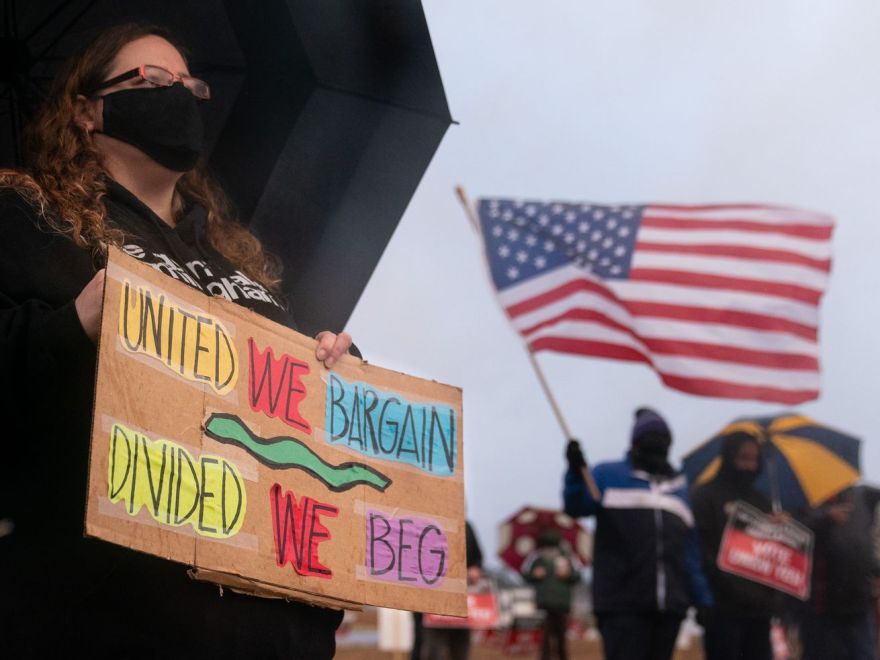 """A protester holds a sign near Amazon's Bessemer, Alabama, warehouse that reads, """"United we bargain, divided we beg."""""""