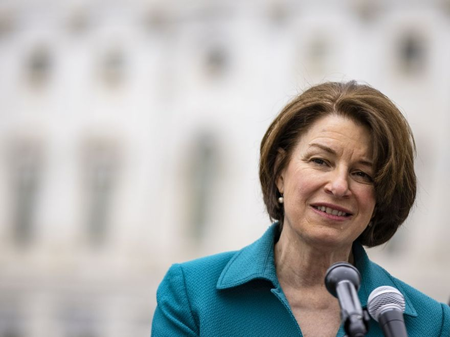 Sen. Amy Klobuchar stands in front of a microphone outside of the US Capitol.