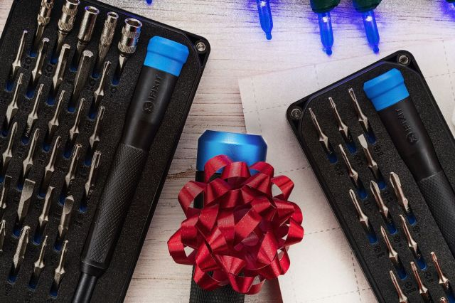 An image of the two new iFixit kits, with a screwdriver wrapped in a bow between them