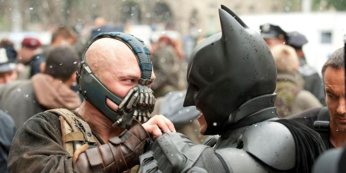 Tom Hardy as Bane and Christian Bale as Batman struggle in The Dark Knight Rises