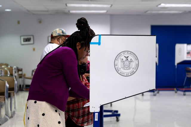 A voting site worker helps a Spanish-speaking elderly woman fill out her ballot at Hostos Community College in The Bronx, June 22, 2021.