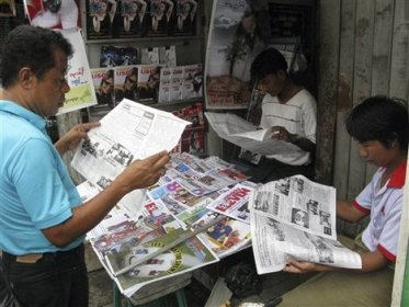 Myanmar men read state-run newspapers at a stall in Yangon, Myanmar Thursday, Aug. 12, 2010. Myanmar's Election Commission has designated constituencies for the national and regional parliaments, state media announced Wednesday, moving a step closer toward the general election promised for sometime this year.
