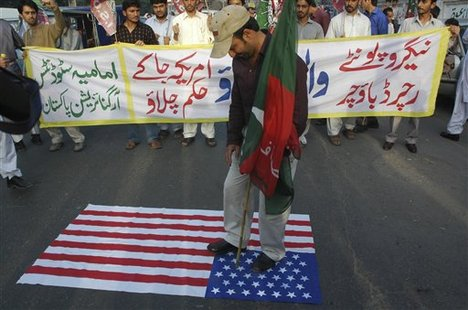 A Pakistani protester stands over the US flag bin front of a a banner which reads 'Negroponte and Boucher go back,' to condemn their visit in Pakistan, on Tuesday, March 25, 2008 in Lahore, Pakistan. American Deputy Secretary of State John Negoroponte and Assistant Secretary of State for South Asia Richard Boucher arrived in Islamabad and held talks with Pakistan's former Prime Minister Nawaz Sharif just as the new premier was sworn i