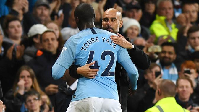 Pelatih Manchester City, Pep Guardiola, memeluk Yaya Toure usai laga melawan Brighton and Hove Albion di Stadion Etihad, Rabu (9/5/2018). Laga tersebut menjadi ajang perpisahan sang pemain bersama The Citizens. (AFP/Paul Ellis)