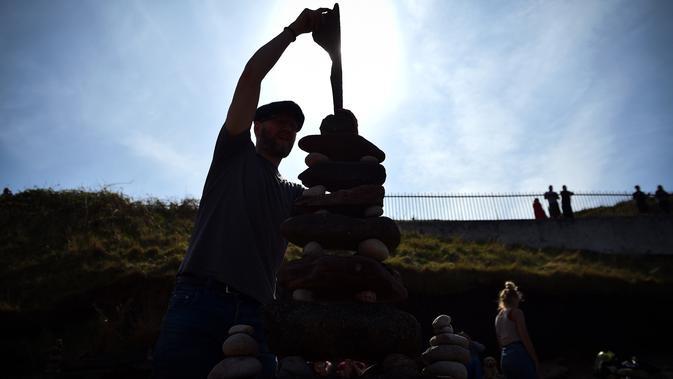 Laurence Winram dari Edinburgh berkompetisi dalam Kejuaraan Menumpuk Batu Eropa 2019 di Dunbar, Skotlandia, Minggu (21/4). Pemenang dalam kejuaraan tersebut akan terbang ke llano Earth Art Festival dan mengikuti World Stone Balancing Competition 2020. (Andy Buchanan / AFP)