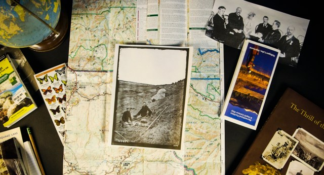 Various printed maps and photographs and books set on a table.