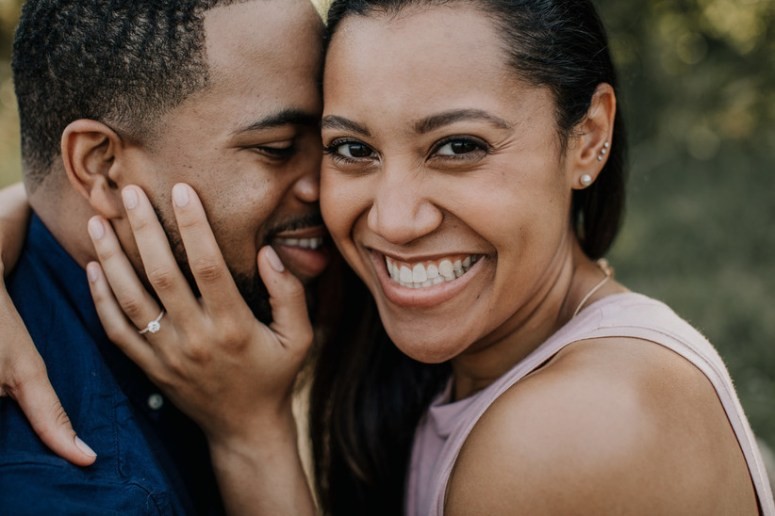 close up portrait of Black couple. she is smiling at the camera while he kisses her cheek