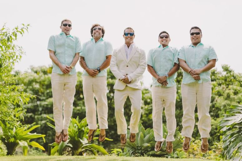 groom and groomsmen jumping destination wedding beach